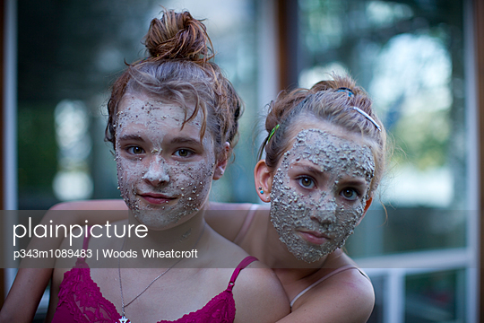 Portrait of two girls with clay facial masks on.