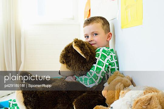 Boy hugging teddy bear in bed