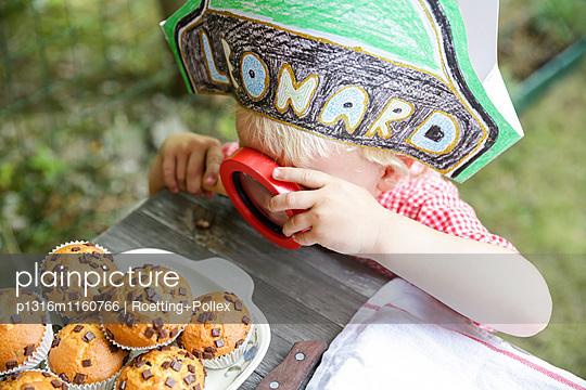 Junge untersucht mit einer Lupe Muffins, Leipzig, Sachsen, Deutschland - p1316m1160766 von Roetting+Pollex