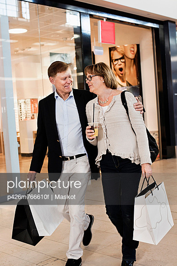 Happy senior couple with shopping bags walking by store in mall