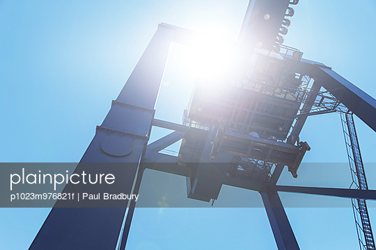 Low angle view of cargo crane against blue sky
