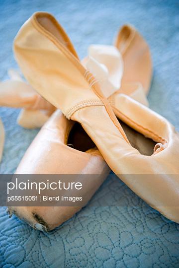 Pink ballet slippers on blue bedspread