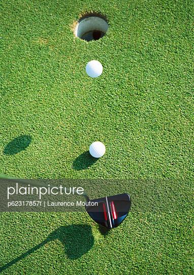 Golf ball in mid air near hole