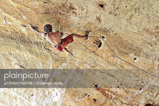 Junger Mann klettert eine Felswand hinauf, Finale Ligure, Savona, Italien - p1316m1160798 von Christoph Jorda