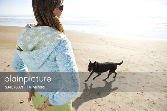 A woman and her dog on beach
