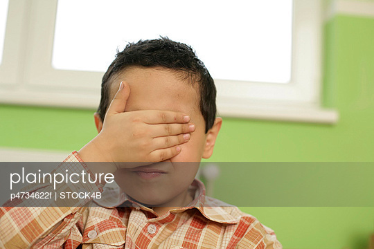 Boy covering his face