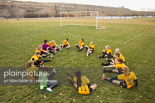 Coach and soccer team stretching on field