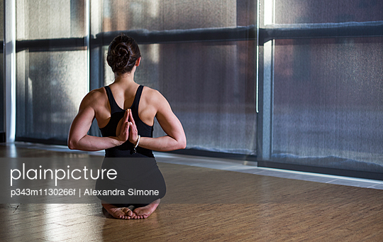 Female Yoga Instructor in Reverse Prayer in the yoga studio