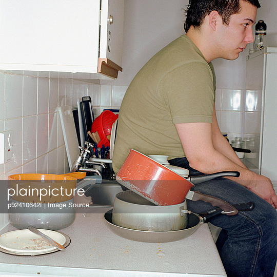 Boy sitting in a messy kitchen
