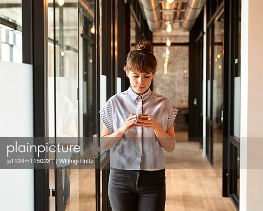 Junge Frau mit Smartphone im Büroflur - p1124m1150231 von Willing-Holtz