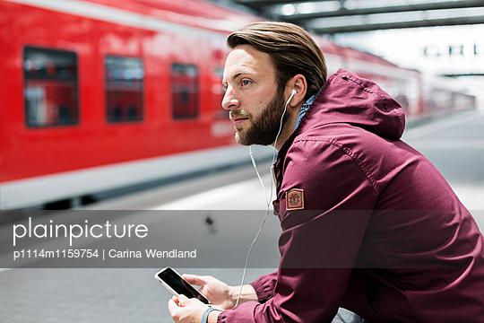 Mann wartet am Bahnhof und hört Musik - p1114m1159754 von Carina Wendland