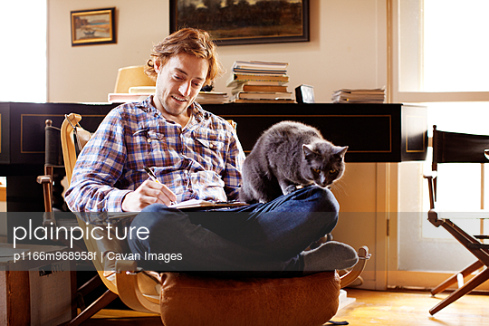 Man Writing With Cat On His Lap