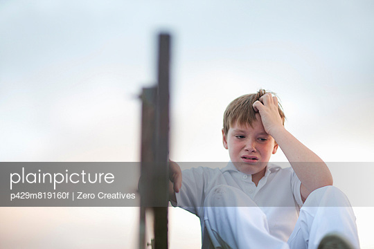 Boy on bleachers at cricket pitch scratching head