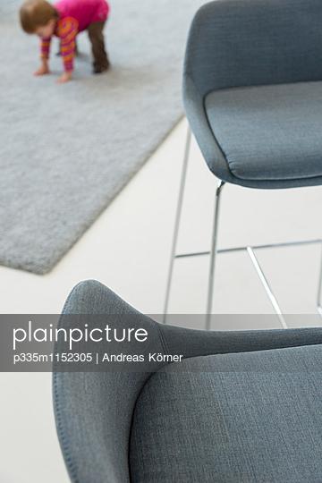 Graue Stühle, im Hintergrund spielt Kleinkind  - p335m1152305 von Andreas Körner