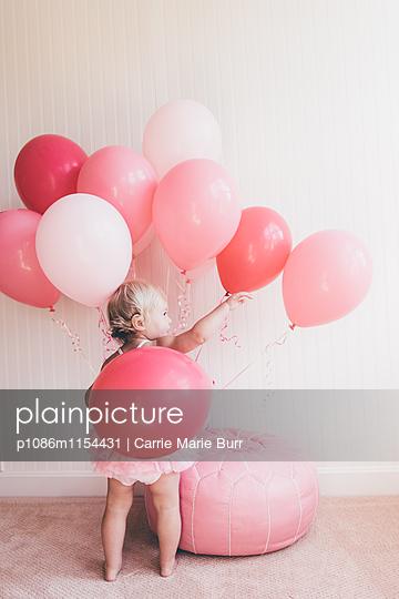 Kleines Mädchen spielt mit Luftballons - p1086m1154431 von Carrie Marie Burr