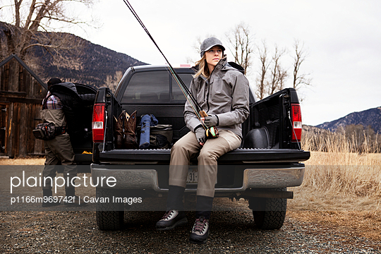 Woman Sitting In Truck With Fishing Rod