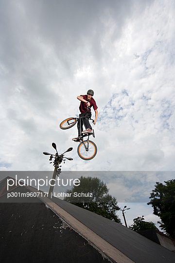 A young man in mid-air doing a stunt on a BMX bike