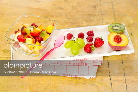 Plastic cup of fruit salad, plastic spoon and fruits on wooden tray