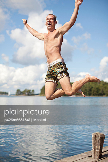 Excited mature man jumping into lake