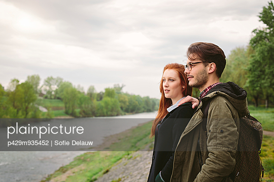 Couple standing in park by river