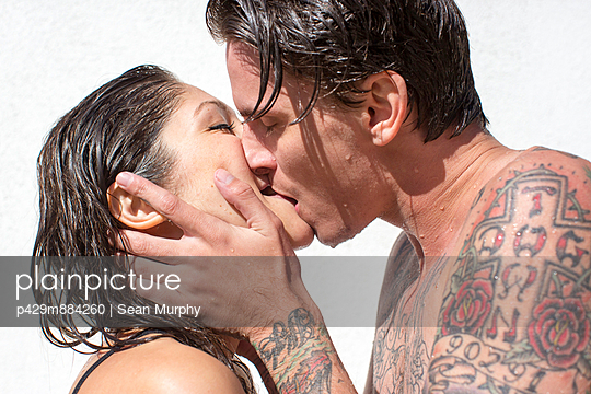 Close up of young couple with wet hair kissing