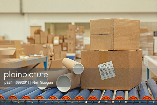 Cardboard boxes and tubes on conveyor belt