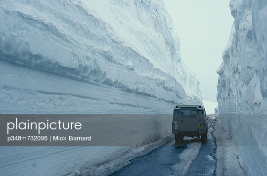 A truck driving through a snowy road, Norway