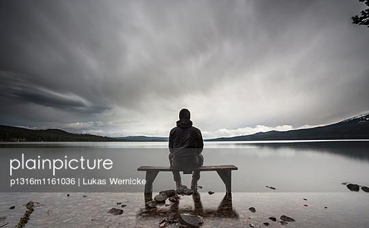 Person sitzt auf einer Bank am See, Douglas County, Oregon, USA - p1316m1161036 von Lukas Wernicke