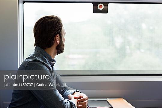 Mann schaut aus dem Zugfenster - p1114m1159737 von Carina Wendland