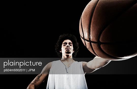 Basketball player holding basketball, low angle