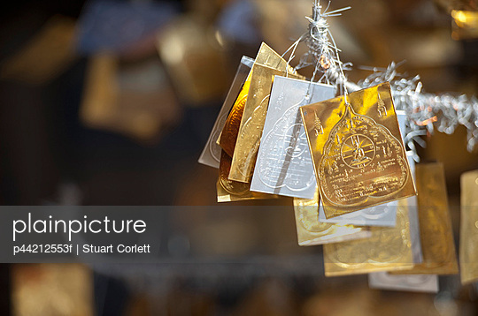 gold and silver merit symbols hanging in doi kham buddhist temple; chiang mai, thailand