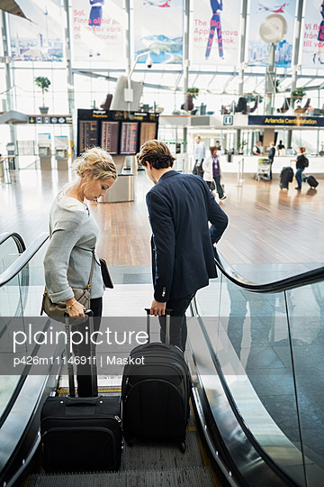 Rear view of business people with luggage moving down escalator at airport