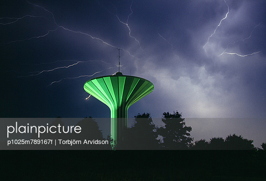 Thunderstorm against mushroom shaped water tower and silhouette trees