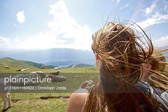 Zwei junge Frauen betrachten eine Herde Kühe, Alpe-Adria-Trail, Nockberge, Kärnten, Österreich - p1316m1160622 von Christoph Jorda