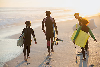 Multi-ethnic family carrying surfboard and boogie boards on sunny summer sunset beach - p1023m1506555 by Sam Edwards