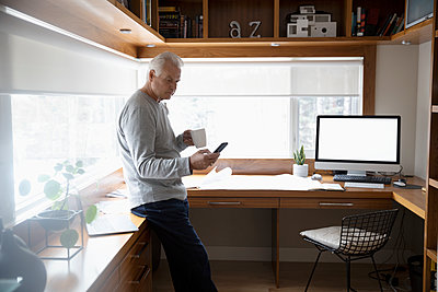 Senior man working from home, drinking coffee and using smart phone in home office - p1192m2088263 by Hero Images