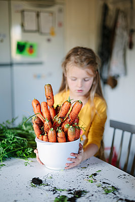 Girl holding bowl with carrots - p312m2191160 by Matilda Holmqvist