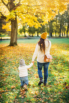 Rear view of mother and son in autumn leaves in Sweden - p352m1536616 by Calle Artmark