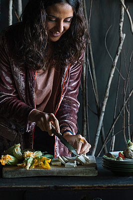 Young woman chopping fresh food on rustic cutting board - p429m2052354 by Alberto Bogo