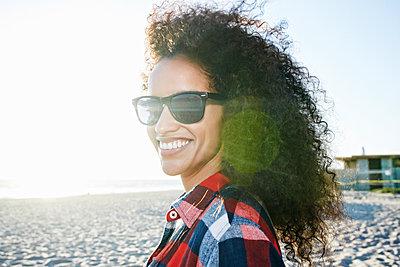 Portrait of smiling Hispanic woman at beach - p555m1303383 by Peathegee Inc