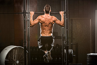 Caucasian man doing chin-up in gymnasium - p555m1303451 by Mike Kemp