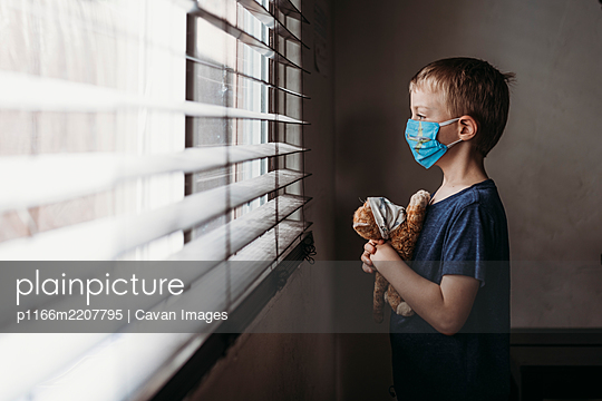 Side view of young school aged boy with mask on with stuffed animal - p1166m2207795 by Cavan Images
