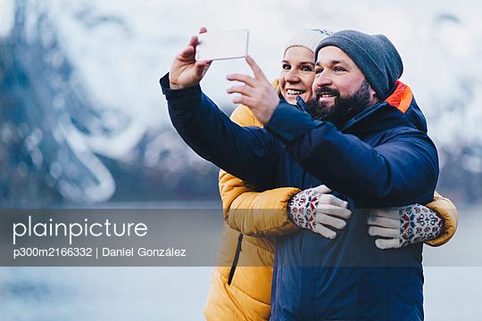 Tourist couple taking a selfie at Hamnoy, Lofoten, Norway - p300m2166332 von Daniel González