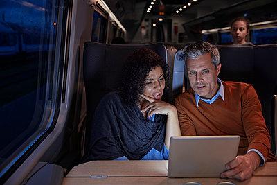 Couple using digital tablet on dark passenger train at night - p1023m1561160 by Agnieszka Olek