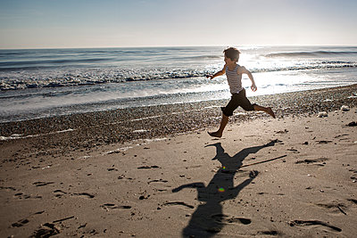 Full length of playful boy running at beach during sunset - p1166m1576687 by Cavan Images