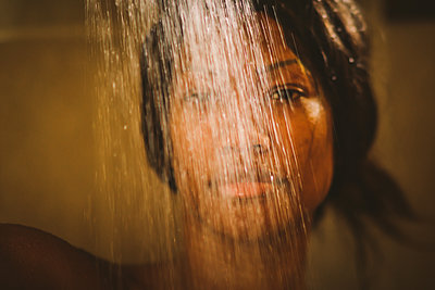 black  sensual Woman in a shower under water - p1166m2129850 by Cavan Images