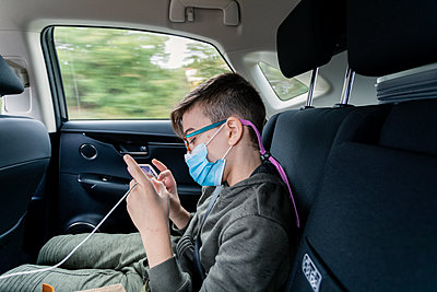 Pre-teen boy wearing mask uses phone in backseat of a moving vehicle - p1166m2246911 by Cavan Images