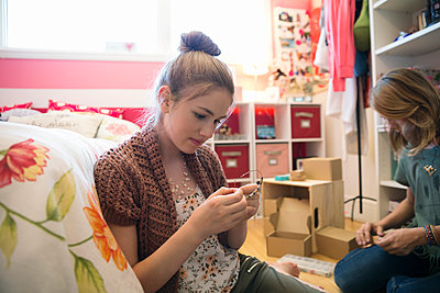 Girls making jewelry in bedroom - p1192m1158034 by Hero Images