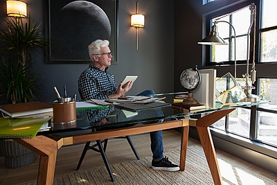 Thoughtful senior man using digital tablet in modern home office - p1192m2047656 by Hero Images