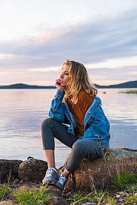 Finland, Lapland, young woman sitting on a rock at the lakeside - p300m2060833 by Kike Arnaiz